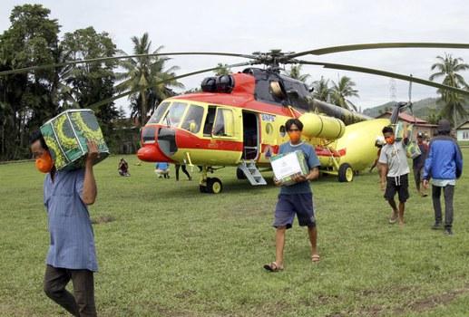 Warga korban gempa membantu mengangkat bantuan logistik yang dikeluarkan dari sebuah helikopter di Majene, Sulawesi Barat, 20 Januari 2021. [AP]