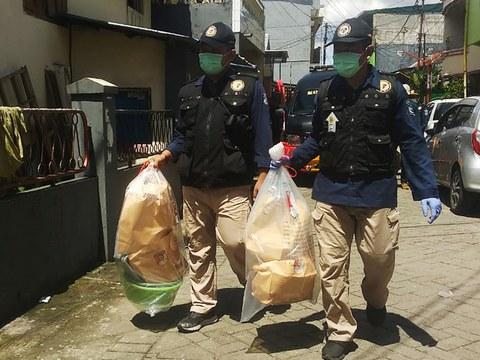 Dua orang petugas membawa plastik berisi sejumlah barang bukti yang disita dari rumah pelaku bom bunuh diri di Gereja Katedral berinisial L di Jalan Bunga Ejaya, Kelurahan Bunga Ejaya, Kecamatan Bontoala, Makassar, Sulawesi Selatan, 29 Maret 2021.