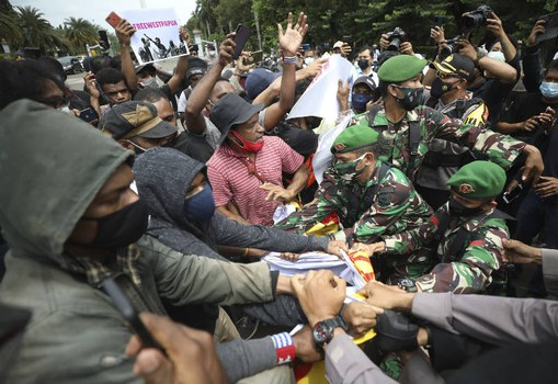 Aktivis Papua bentrok dengan tentara dan petugas polisi yang mencoba menyita spanduk mereka dalam demonstrasi menuntut kemerdekaan Papua, di Jakarta, 19 Desember 2020. [AP]