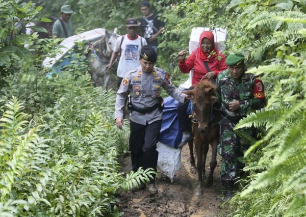 Polisi dan tentara ikut menjaga kotak suara yang diangkut dengan kuda ke TPS-TPS di sejumlah desa di Tempurejo, Jawa Timur, 15 April 2019. (AP)