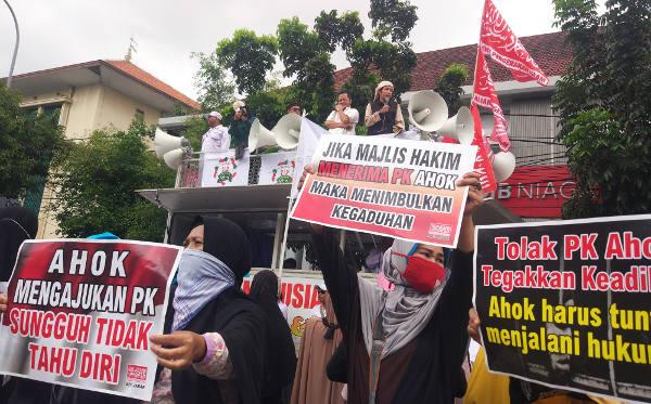Massa penentang Ahok membawa poster dan berorasi di luar Pengadilan Negeri Jakarta Utara, 26 Februari 2018. (Rina Chadijah/BeritaBenar)