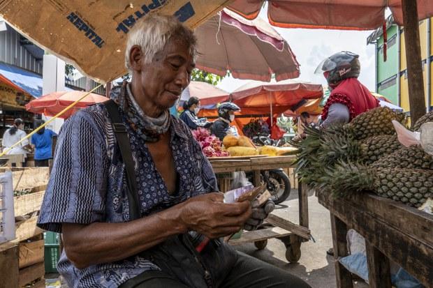 Seorang pedagang buah menghitung pendapatannya sementara menunggu pembeli di sebuah pasar di Jakarta, 31 Mei 2020. Masyarakat yang sulit mengakses pinjaman ke bank, kadang akhirnya menjadi korban pinjaman online dengan bunga yang mencekik leher.