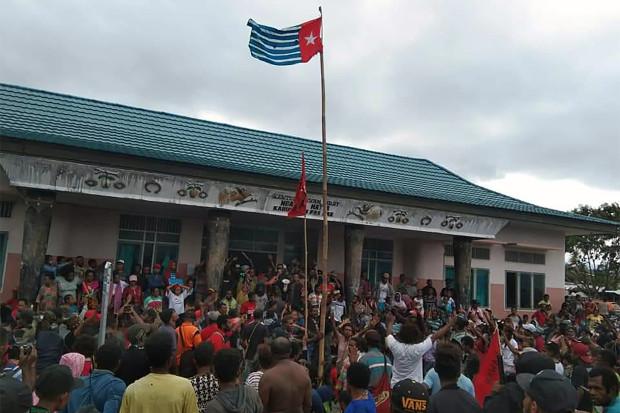 Para pengunjuk rasa berkumpul di bawah kibaran bendera Bintang Kejora yang dilarang pemerintah Indonesia, di Fakfak Papua, 21 Agustus 2019. [AFP]