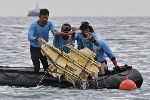 Penyelam TNI AL mengangkat bagian dari bangkai pesawat Sriwijaya Air penerbangan SJ-182 dalam operasi pencarian dan penyelamatan di laut dekat pulau Lancang, Kepulauan Seribu, pada 10 Januari 2021. [AFP]