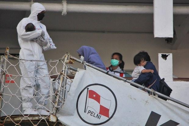Seorang tenaga kesehatan menggendong seorang bayi ketika sebuah keluarga menaiki kapal Umsini, yang diubah menjadi pusat isolasi COVID-19, di Makassar, Sulawesi Selatan, 2 Agustus 2021.
