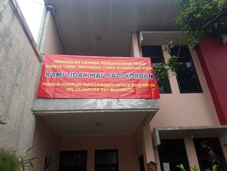 Sebuah spanduk di rumah salah seorang warga di perumahan Margawangi Estate di Kota Bandung yang lokasinya berada di dekat proyek kereta cepat Jakarta-Bandung. [Dok. Sri Rama Aryadhana]
