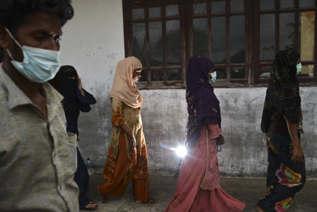 Sejumlah pengungsi Rohingya mengantri setelah melakukan proses identifikasi di tempat penampungan mereka di bekas Kantor Imigrasi Lhokseumawe, Aceh, 26 Juni 2020. [AFP]