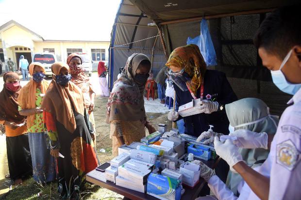 Gambar yang diambil pada 9 September 2020 ini menunjukkan sekelompok wanita Rohingya mengantri untuk pemeriksaan kesehatan di kamp penampungan mereka di Lhokseumawe, Aceh.
