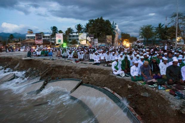 Warga mengadakan salat bersama di Palu pada 12 Oktober 2018, dua minggu setelah terjadinya gempa dan tsunami pada 28 September yang menewaskan 2.000 orang dan ribuan orang dinyatakan masih hilang. (AFP)