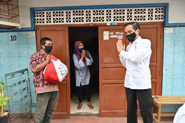 Presiden Joko Widodo mengucapkan salam setelah memberikan paket sembako ke warga yang terdampak pandemi COVID-19 di Jakarta, 18 Mei 2020. [AFP]