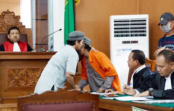 Saksi Saiful Muthohir (kiri) berpelukan dengan terdakwa kasus terorisme Aman Abdurrahman menjelang persidangan di Pengadilan Negeri Jakarta Selatan, 6 Maret 2018. (Arie Firdaus/BeritaBenar)