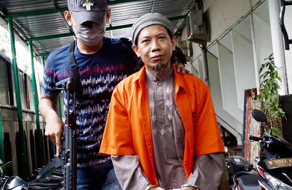 Terdakwa kasus terorisme Aman Abdurrahman dikawal aparat bersenjata memasuki Pengadilan Negeri Jakarta Selatan, 6 Maret 2018. (Arie Firdaus/BeritaBenar)