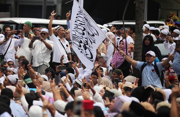 Seorang pendukung calon presiden Prabowo Subianto membawa bendera bertuliskan kalimat Tauhid saat acara syukuran kemenangan di Jakarta, 19 April 2019. (Keisyah Aprilia/BeritaBenar)