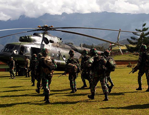 Tentara Indonesia membawa senjata mereka ketika berjalan menuju helikopter untuk terbang ke kecamatan Nduga, Wamena, Papua, tanggal 5 Desember 2018. (Antara Foto/Iwan Adisaputra via Reuters)