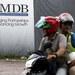Dua individu menaiki motosikal melewati papan iklan 1MDB di kawasan pembangunan Tun Razak Exchange di Kuala Lumpur, 3 Feb 2016.