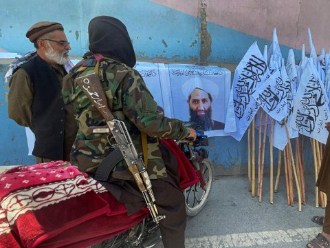 Anggota-anggota Taliban berkumpul berhampiran gambar Mullah Haibatullah Akhundzada, yang kini menjadi pemimpin tertinggi Afghanistan, di Kabul, 25 Ogos 2021.