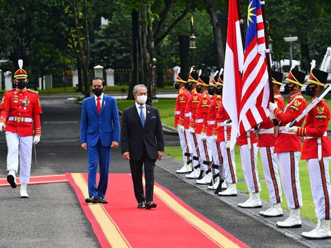 Presiden Indonesia Joko Widodo (dua dari kiri) dan Perdana Menteri Malaysia Muhyiddin Yassin memeriksa perbarisan kehormatan di Istana Presiden di Jakarta, 5 Februari 2021.