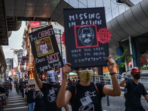 Peserta protes memegang sepanduk menggesa Perdana Menteri Muhyiddin supaya meletak jawatan, ketika satu demonstrasi berhampiran Dataran Merdeka di Kuala Lumpur, 31 Julai 2021.