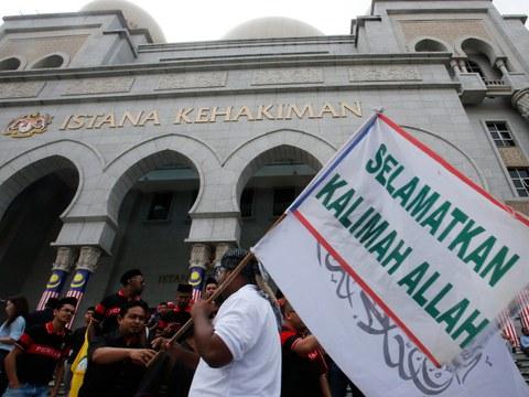 Lelaki Islam bersama dengan bendera pasa satu tunjuk perasaan di hadapan bangunan Mahkamah Rayuan di Putrajaya, Malaysia, 22 Ogos 2013.