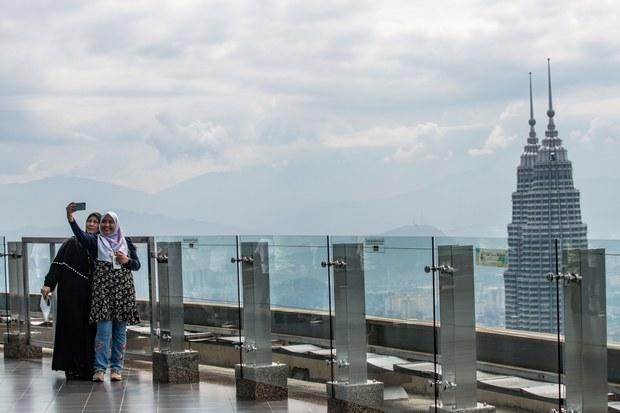 Wanita Malaysia sedang mengambil gambar secara 'selfie' yang berlatar belakangkan Menara Berkembar Petronas dari Menara KL di Kuala Lumpur, 24 Julai 2020.