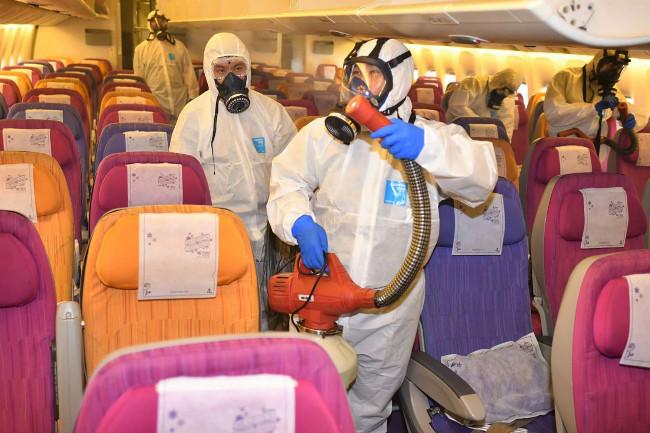 ลูกเรือพ่นยาฆ่าเชื้อในห้องผู้โดยสารของสายการบินไทย หนึ่งในขั้นตอนป้องกันการแพร่กระจายของเชื้อโคโรนาไวรัส ที่สนามบินสุวรรณภูมิ กรุงเทพฯ วันที่ 28 มกราคม 2563 (การบินไทย/เอเอฟพี)