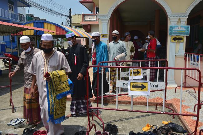 ชายชาวมุสลิม ขณะออกจากมัสยิดหลังพิธีละหมาดเป็นวันศุกร์แรกในรอบสองเดือน ที่รัฐบาลให้ปิดมัสยิดชั่วคราว ในห้วงป้องกันการแพร่กระจายของโควิด-19 จังหวัดนราธิวาส วันที่ 22 พฤษภาคม 2563 (เอเอฟพี)