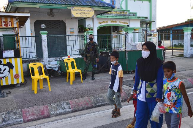 ผู้หญิงเดินจูงเด็ก ๆ เดินผ่านสมาคมอิสลาม จังหวัดนราธิวาส เพื่อไปซื้ออาหารที่ตลาด ก่อนละศีลอด ในช่วงเดือนรอมฎอน จังหวัดนราธิวาส วันที่ 5 พฤษภาคม 2563 (เอเอฟพี)