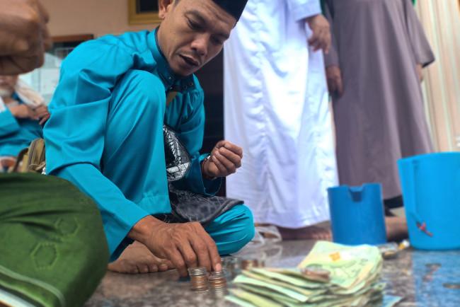 นายรอพี สาและยีงอ นับเงิน ก่อนนำไปแจกให้เด็ก ๆ ที่รอรับเงินบริจาค ด้านหน้ามัสยิดบ้านเจาะกลาดี อำเภอยะหา จังหวัดยะลา วันที่ 31 กรกฎาคม 2563 (มารียัม อัฮหมัด/เบนาร์นิวส์)