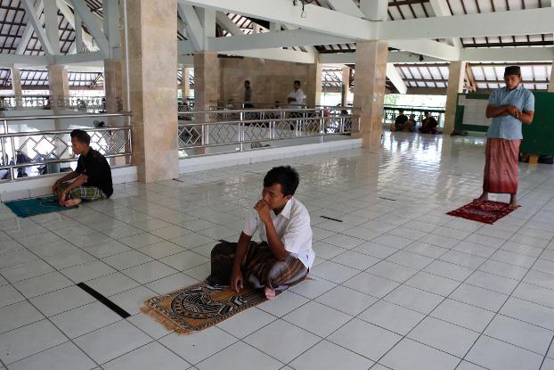 ชาวมุสลิมนั่งเว้นระยะห่างกันตามมาตรการเว้นระยะห่างทางสังคม ขณะร่วมละหมาดในวันศุกร์ ที่มัสยิดแห่งหนึ่งในเกาะบาหลี ประเทศอินโดนีเซีย เพื่อป้องกันการแพร่ระบาดของโควิด-19 วันที่ 20 มีนาคม พ.ศ. 2563 (เอพี)
