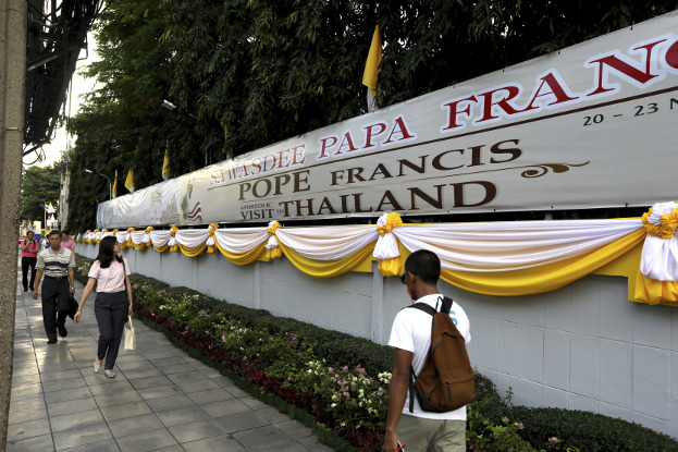ผู้คนเดินผ่านป้ายต้อนรับสมเด็จพระสันตะปาปาฟรานซิส ที่กรุงเทพฯ ประเทศไทย วันที่ 19 พฤศจิกายน 2562 (เอพี)