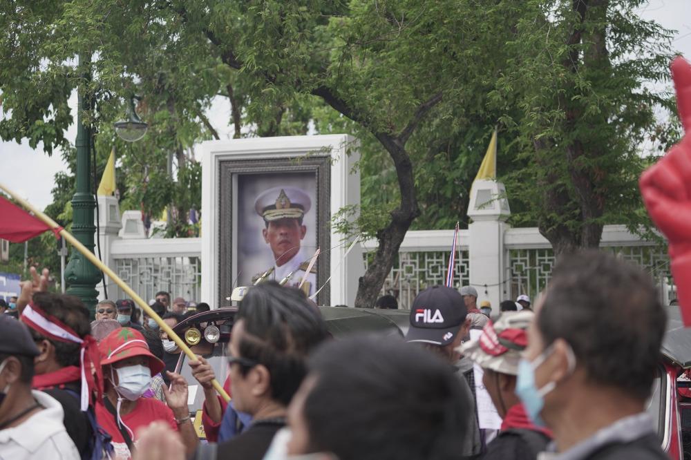 ผู้ประท้วงต่อต้านรัฐบาลเดินผ่านพระบรมฉายาลักษณ์ของพระบาทสมเด็จพระวชิรเกล้าเจ้าอยู่หัว ในกรุงเทพฯ วันที่ 19 กันยายน 2563 (นนทรัฐ ไผ่เจริญ/เบนาร์นิวส์)