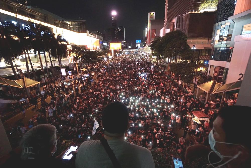 กลุ่มต่อต้านรัฐบาลหลายพันคนรวมตัวกันอีกครั้ง ที่ย่านราชประสงค์ ในตอนเย็นของวันพฤหัสบดีนี้ หลังจากที่เจ้าหน้าที่ตำรวจได้สลายการชุมนุมที่ด้านข้างทำเนียบรัฐบาลไปเมื่อตอนเช้า วันที่ 15 ตุลาคม 2563 (นนทรัฐ ไผ่เจริญ/เบนาร์นิวส์)