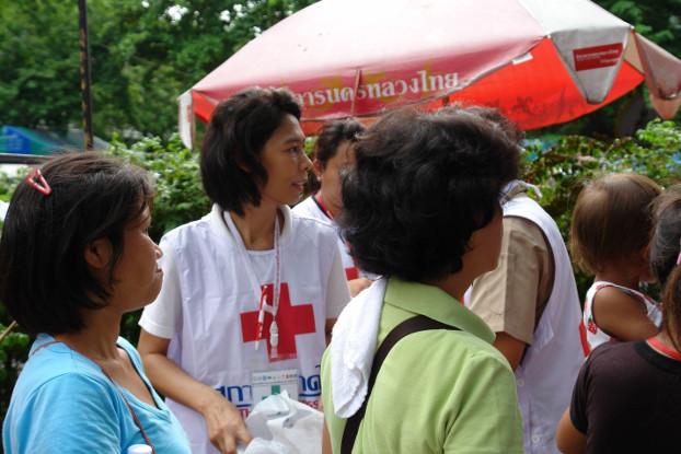 สมาชิกสภากาชาดไทยแจกอาหารและอุปกรณ์การแพทย์แก่กลุ่มผู้ประท้วง ที่วัดปทุมวนาราม ในกรุงเทพฯ สองวันก่อนที่อาสาสมัครและผู้ประท้วงถูกยิง ภาพเมื่อวันที่ 17 พฤษภาคม 2553 (ภิมุข รักขนาม/เบนาร์นิวส์)