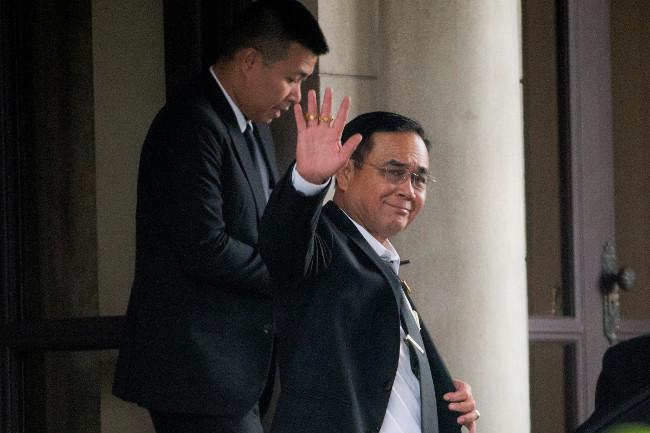 พลเอกประยุทธ์ จันทร์โอชา นายกรัฐมนตรี โบกมือให้สื่อมวลชนที่มารอทำข่าว ก่อนออกจากทำเนียบรัฐบาล กรุงเทพฯ ตอนเย็นวันพุธที่ 5 มิถุนายน 2562 (เอพี)