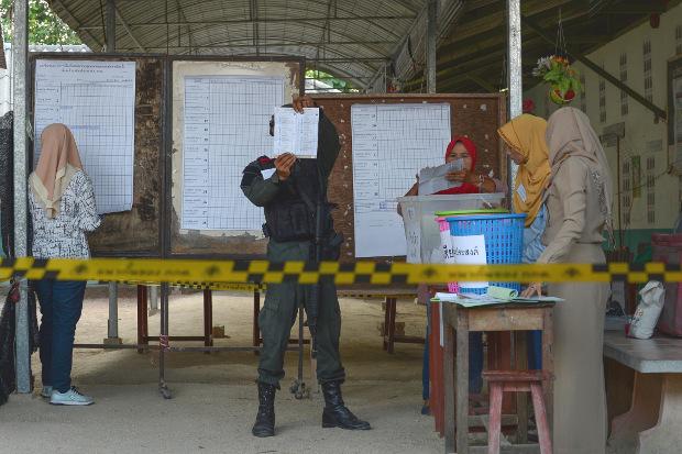 เจ้าหน้าที่ตำรวจ ทหารและเจ้าหน้าที่หน่วยเลือกตั้งร่วมนับคะแนนที่คูหาเลือกตั้ง หลังจากปิดหีบเลือกตั้ง จังหวัดนราธิวาส วันที่ 24 มีนาคม 2562 (เอเอฟพี)
