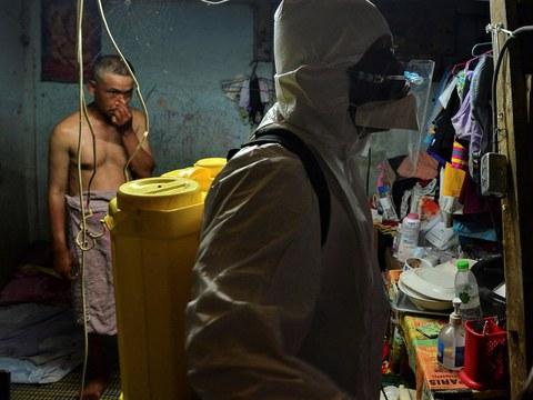 เจ้าหน้าที่หน่วยบรรเทาสาธารณภัยสุนทร ฉีดพ่นน้ำยาฆ่าเชื้อในบ้านผู้ติดเชื้อโควิด-19 ภายในชุมชนพัฒนาใหม่ คลองเตย กรุงเทพฯ หลังจากได้ส่งต่อผู้ติดเชื้อไปโรงพยาบาลแล้ว วันที่ 1 พฤษภาคม 2564