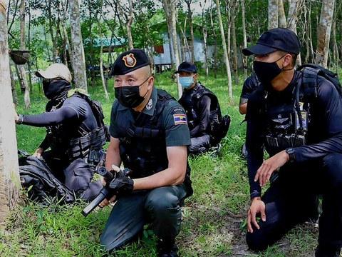 เจ้าหน้าที่ตำรวจนั่งระวังเหตุในระหว่างการปิดล้อมเป้าหมายผู้ต้องสงสัยในบ้านชะเมาสามต้น อำเภอสายบุรี จังหวัดปัตตานี วันที่ 5 กรกฏาคม 2562