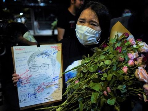 นางสุรีย์รัตน์ ชิวารักษ์ แม่ของนายพริษฐ์ หรือ เพนกวิน รับดอกไม้จากผู้สนับสนุน ขณะประท้วงเรียกร้องให้ปล่อยตัวลูกชายและนักกิจกรรมทั้งหมด ที่ถูกจับกุมในคดีมาตรา 112 ที่มหาวิทยาลัยแห่งหนึ่ง ในกรุงเทพฯ วันที่ 10 มีนาคม 2021